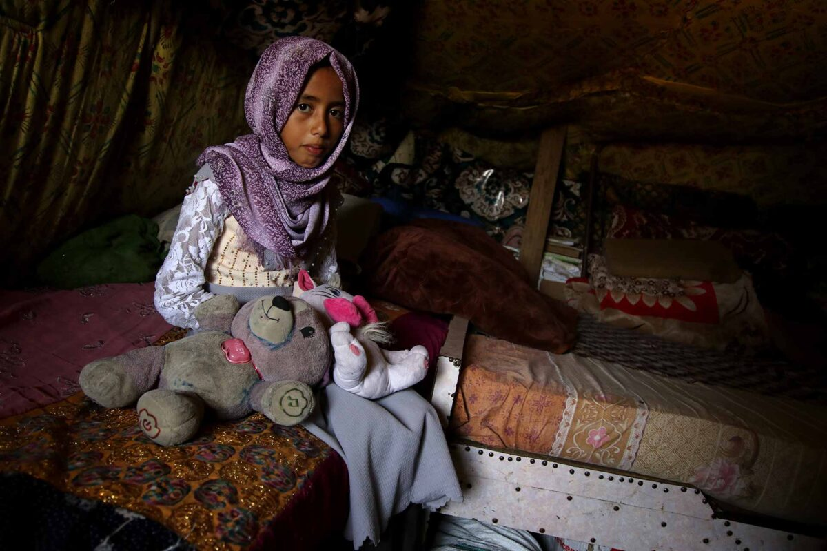 A displaced Yemeni girl surrounded by teddy bears in the tent