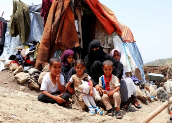 A displaced mother and her 5 children sitting outside their tent