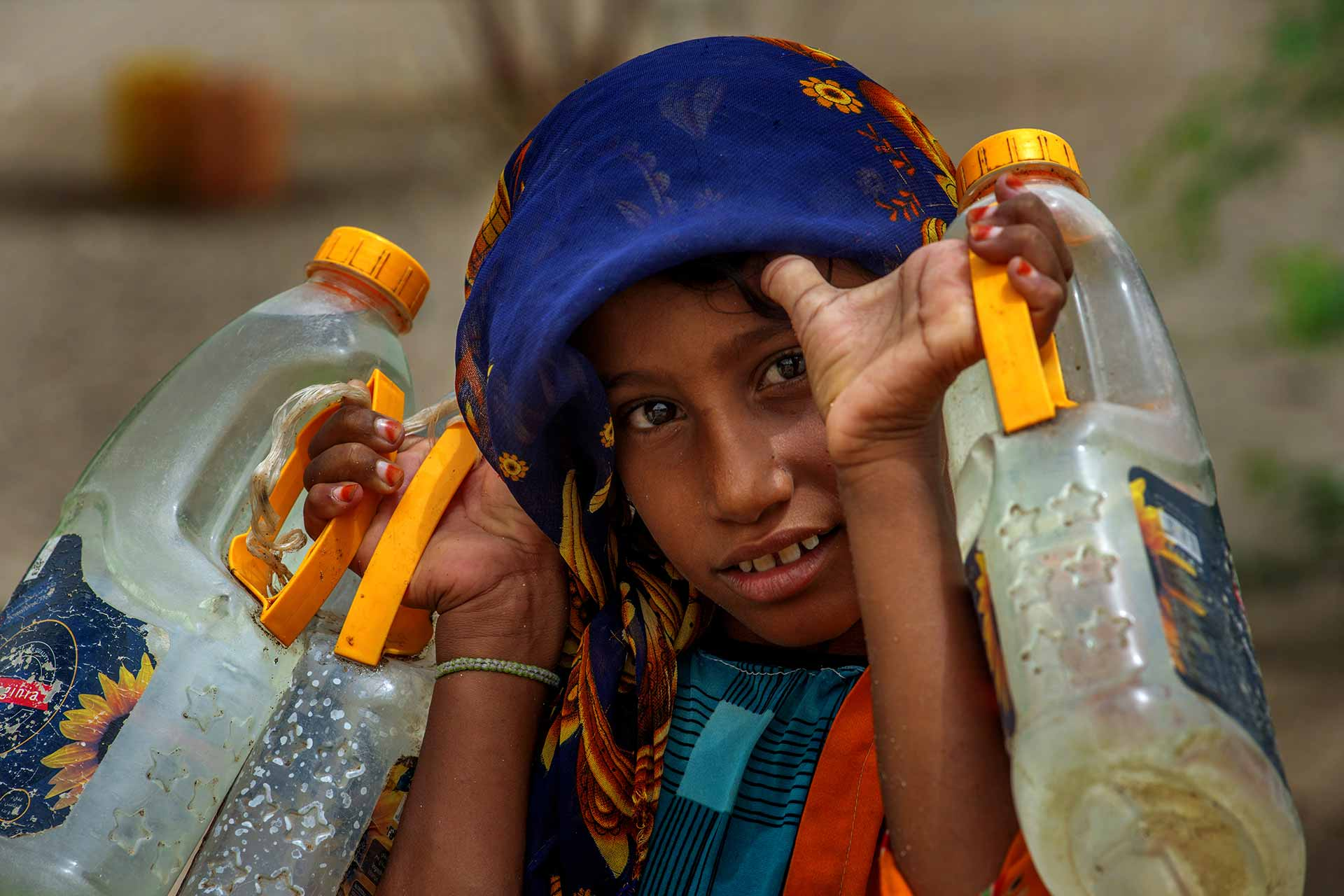 A young Yemeni fetches water at a makeshift camp